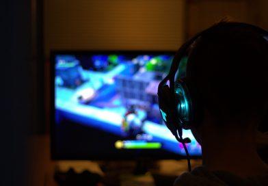 chłopak grający w grę komputerową, odwrócony i w słuchawkach, patrzy na jasny ekran