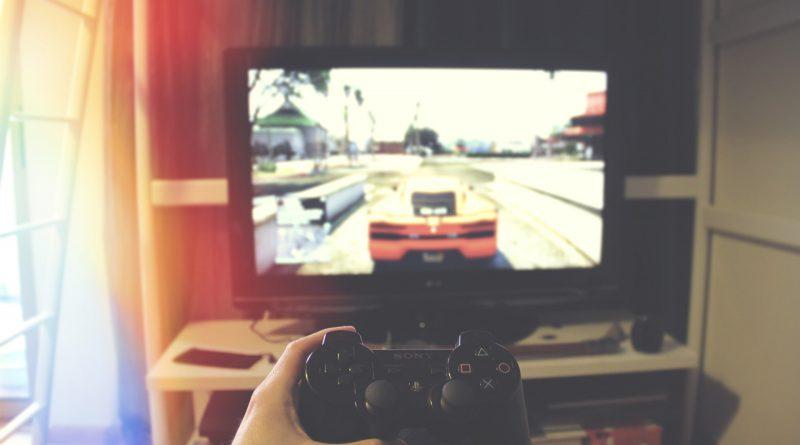widok z pierwszej osoby, osoba trzyma kontroler do konsoli i patrzy na telewizor, na nim gra wyścigowa