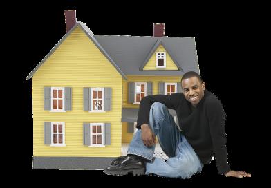czarnoskóry mężczyzna siedzi przed zabawkowym domem, uśmiecha się