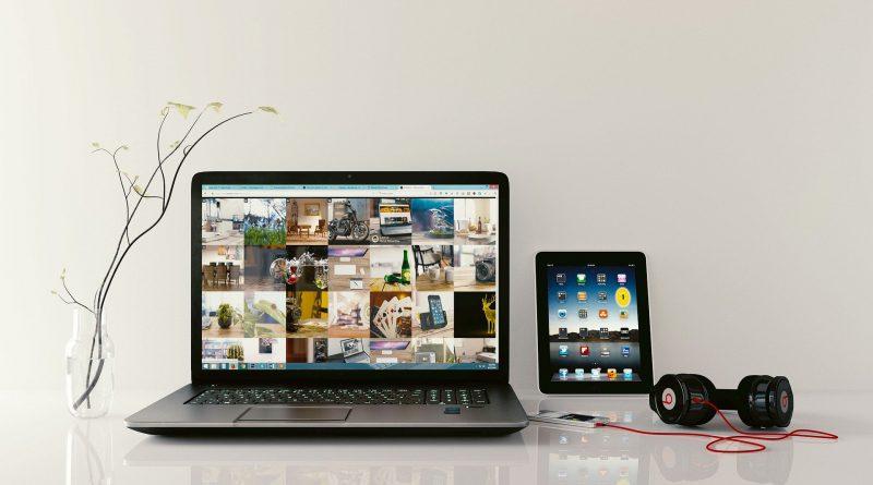 Laptop z wynajmu laptopów biznesowych leży na stole wraz z tabletem, słuchawkami i wazonem.
