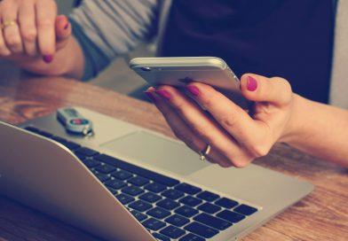 laptop uzyskany poprzez wypożyczenie laptopa leży na biurku. Przy nim kobieta, która w ręku trzyma telefon